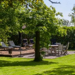 Ruime tuin met zitjes voor groepen, grote terrastafels, chillen